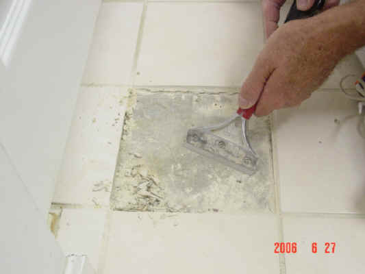 Scraping off tile adhesive from floor